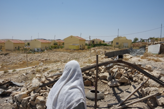 Sulieman looks across the demolition to the settlement of Karmel