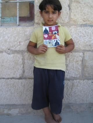 Bara's brother Kossi holds a printout of  photos he has of Bara. Credit: EAPPI/E.Brightwell