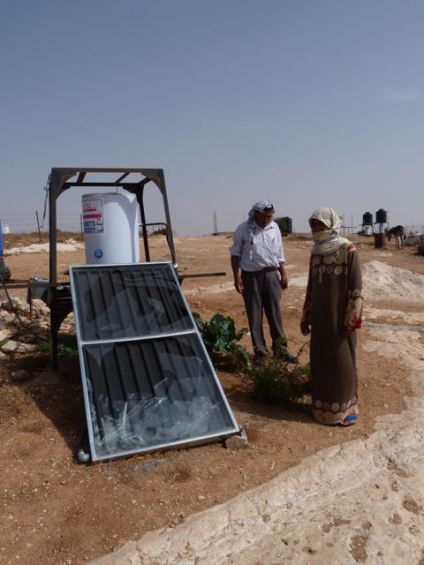 Wife of Naim Nasser Azazmi with solar water heater broken by settlers [Photo_ EAPPI_V.Pasteur] (2)