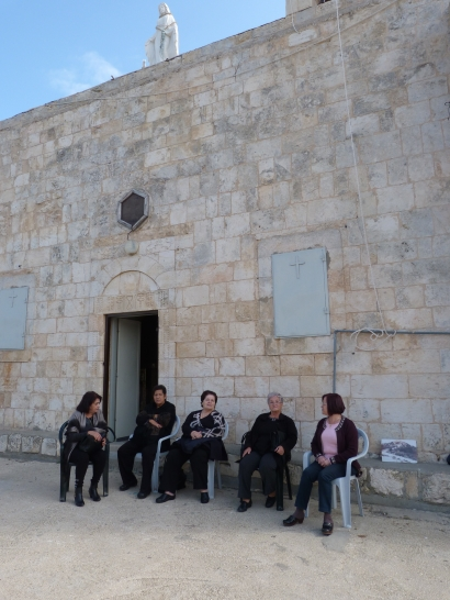 Women sitting and chatting outside the church before mass [Photo: EAPPI/V.Pasteur]
