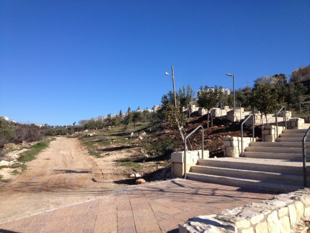 Asphalted pathway leading to Kiryat Arba next to an unpaved pathway leading to Palestinian houses in Wadi Al Hussein (Photo: EAPPI/Sabrina Tucci)
