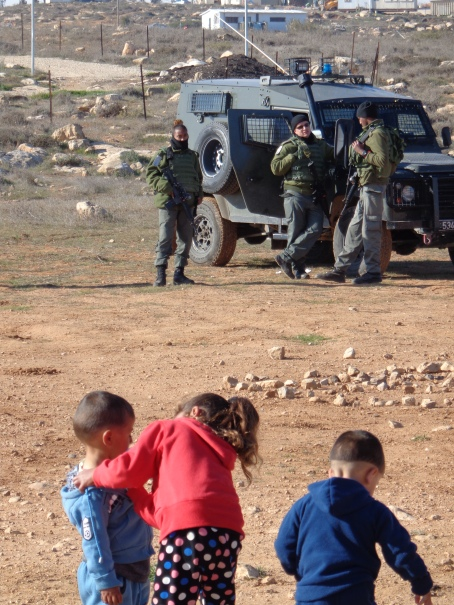 Children play under the watchful eyes of the soldiers
