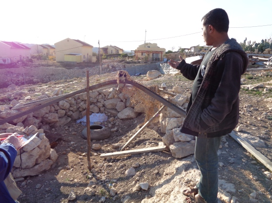 Eidh's grandson, Tariq, showing the demolished communal oven