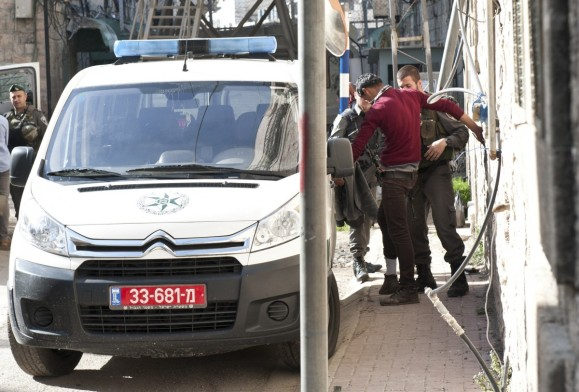 Israeli soldiers body searching a Palestinian man in Hebron [Photo: EAPPI/P.Morgan]