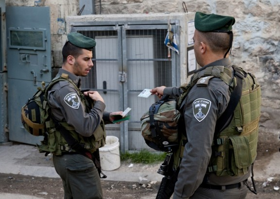 Israeli soldiers checking Palestinians' IDs [Photo: EAPPI/P.Morgan]