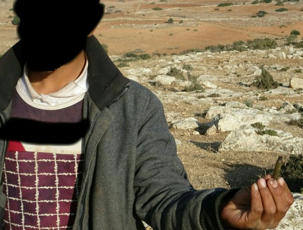 North Jordan Valley, Khirbet Yarza. Palestinian resident shows cartridge case found adjacent to his house.