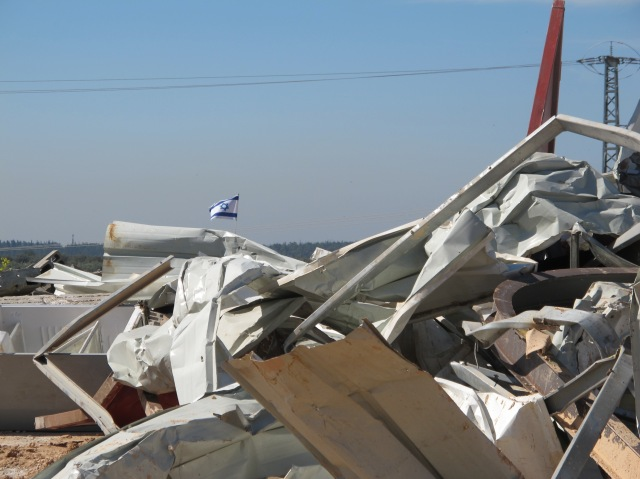 The Israeli flag flying from the top of an army watchtower behind the destruction. Photo: EAPPI  EA Marie