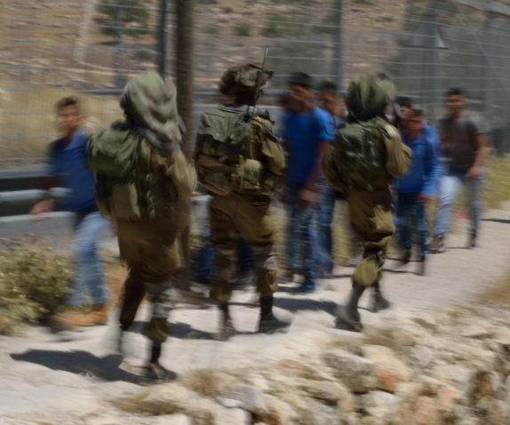 02-05-2016 Tuqu Secondary School Boys walk home past Israeli soldiers EAPPI K Fox