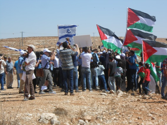 palestinians-from-susiya-hold-up-their-flags-in-protest-at-the-settler-visit-onto-their-land