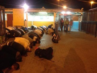 Men pray in waiting area at Qalandiya checkpoint Photo:EAPPI/Augustina